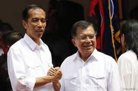 """Indonesian presidential candidate Joko """"Jokowi"""" Widodo (L) and his vice presidential running mate Yusuf Kalla shake hands during an event declaring their bid in the upcoming July 9 election, in Jakarta, May 19, 2014."""