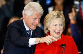 Former President Bill Clinton, left, and Democratic presidential candidate Hillary Clinton acknowledge supporters during a caucus night rally at Drake University in Des Moines, Iowa, Feb. 1, 2016.