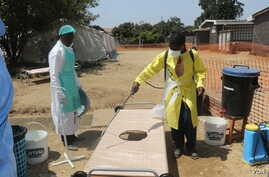 An official disinfects a bed for patients a temporary shelter in Harare, Sept. 12, 2018, where suspected cholera patients are being treated. (C. Mavhunga/VOA)