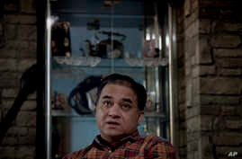 In this Feb. 4, 2013 photo, Ilham Tohti, an outspoken scholar of China's Turkic Uighur ethnic minority, pauses during an interview at his home in Beijing, China. Tohti was set to go on trial on separatism charges on Wednesday, Sept. 17, 2014.