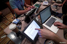 Hackers try to access and alter data from an electronic poll books in a Voting Machine Hacking Village during the Def Con hacker convention in Las Vegas, July 29, 2017.