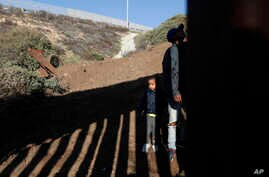 A young Honduran migrant waits for his parents to cross over the U.S. border wall after he was squeezed through one of its gaps, from Playas de Tijuana, Mexico, Dec. 12, 2018.