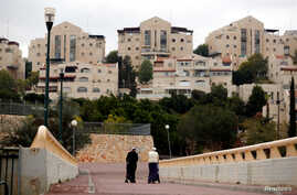 A couple walk in the Israeli settlement of Maale Edumim, in the occupied West Bank December 24, 2016.