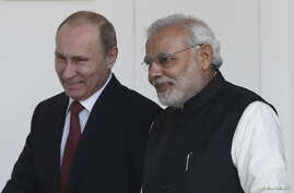 Russian President Vladimir Putin (L) and India's Prime Minister Narendra Modi arrives for a photo opportunity ahead of their meeting at Hyderabad House in New Delhi, December 11, 2014.
