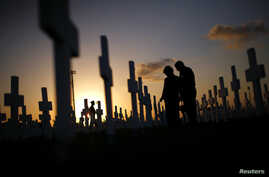 FILE - A couple grieves at a grave in a cemetery Coral Gables, Florida, Feb. 16, 2008. A new study shows that suicide rates in the U.S. jumped 24 percent between 1999 and 2014.
