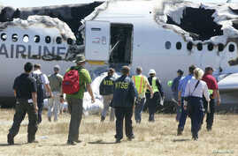 U.S. National Transportation Safety Board (NTSB) investigators are seen working at the scene of the Asiana Airlines Flight 214 crash site at San Francisco International Airport in this handout photo released on July 7, 2013.