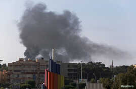 Black smoke billows in the sky above areas where clashes are taking place between pro-government forces and an alliance of former anti-Moammar Gaddafi rebels, in Benghazi, Nov. 26, 2014.