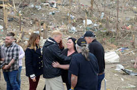 U.S. President Donald Trump is hugged by a resident who survived a tornado, as first lady Melania Trump stands by, in Beauregard, Alabama, March 8, 2019.