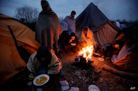 Migrants eat around a fire at a camp in Velika Kladusa, Bosnia, close to the border to Croatia, Nov. 18, 2018.