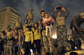 Egyptian Army soldiers celebrate with children on their armored personnel carrier, as they celebrate the news of the resignation of President Hosni Mubarak,  Feb. 11, 2011