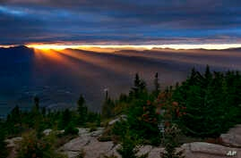 FILE - Sun rays spill through a gap between the clouds and the White Mountains as the skies begin to clear above Bartlett, N.H., Sept. 22, 2017. The first weekend of autumn in the area was unusually warm — and across the nation, the year's first free