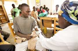 A Rwandan youth is tested for the AIDS virus before he receives a free male circumcision at the Shingiro Health Center in Musanze. (Courtesy the Global Fund)
