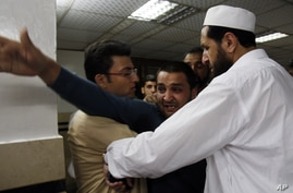 People comfort a man at a local hospital, who lost two cousins in an attack in Peshawar, Pakistan, April 29, 2013.