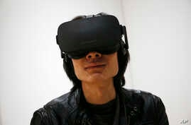 FILE - Peijun Guo wears the Oculus Rift VR headset at the Oculus booth at CES International in Las Vegas, Jan. 6, 2016.   Facebook CEO Mark Zuckerberg seems to be realizing that the headsets his company's Oculus division has been making are too expen