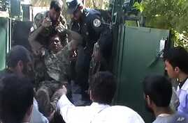 Injured Afghan National Army soldier removed from military vehicle outside local hospital following courthouse attack in Farah province, April 3, 2013.