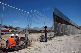 FILE - A boy looks at U.S. workers building a section of the U.S.-Mexico border wall at Sunland Park, N.M., opposite the Mexican border city of Ciudad Juarez, Mexico, Sept. 9, 2016. Picture taken from the Mexico side of the U.S.-Mexico border.
