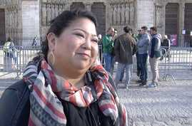 American tourist Dawn Mabalon stands in front of Notre Dame Cathedral in Paris, France, Nov. 15, 2015. (Photo - L. Bryant/VOA)