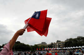 An audience waves Taiwanese flags during the National Day celebrations in Taipei, Taiwan, Oct. 10, 2018.