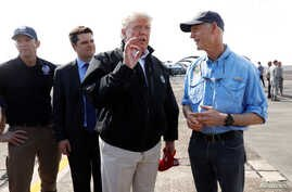 U.S. President Donald Trump stands with  FEMA Administrator Brock Long (L) and U.S. Rep Ron DeSantis (R-FL) as he talks to Florida Governor Rick Scott (R) after the president arrived to tour storm damage from Hurricane Michael at Eglin Air Force Base
