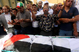 Palestinian men pray over the body of Saed Dawabsha, the father of a Palestinian toddler killed last week when their home was firebombed by suspected Jewish extremists, during his funeral in the West Bank village of Duma, Aug. 8, 2015.