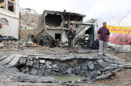 Men stand next to a crater made by a car bomb attack near the presidential palace in the southern port city of Aden, Yemen, Jan. 28, 2016.