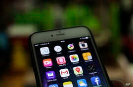 A Gmail mobile app, center left, are seen on a smartphone in Beijing, Dec. 29, 2014.