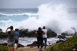 Onlookers watch large waves crash on the rocks at Wawamalu Beach,  Aug. 24, 2018, in Waimanalo, Hawaii.