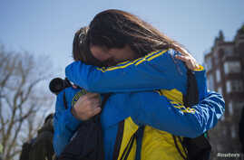 Boston Marathon runners Lisa Kresky-Griffin and Tammy Snyder (L) embrace at the barricaded entrance at Boylston Street near the finish line, April 16, 2013.