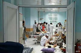 In this undated photograph released by Doctors Without Borders (MSF) on October 3, 2015, Afghan MSF medical personnel treat civilians injured following an offensive against Taliban militants by Afghan and coalition forces at the MSF hospital in Kundu