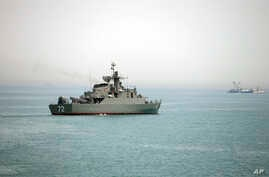 FILE - In this picture taken April 7, 2015, and released by the semiofficial Fars News Agency, the Iranian warship Alborz, foreground, prepares before leaving Iran's waters, at the Strait of Hormuz. Located on the eastern edge of the Persian Gulf, th