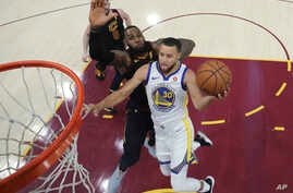 Golden State Warriors' Stephen Curry shoots next to Cleveland Cavaliers' LeBron James during the second half of Game 3 of basketball's NBA Finals, June 6, 2018, in Cleveland.
