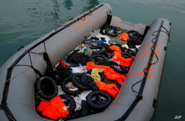 FILE - A dinghy with floats and life-vests of migrants, intercepted aboard of it off the coast in the Mediterranean Sea, is seen after they arrived on a rescue boat at dawn at the port of Malaga, southern Spain, Jan. 15, 2019.