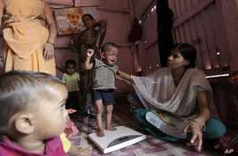 FILE - A volunteer weighs a malnourished child at the Apanalay center in Mumbai, India. A new study indicates in the same way that lack of food can harm children, violence, deprivation and neglect are also damaging their brain circuitry.
