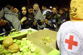 FILE - Hungarian Red Cross workers provide food for migrants walking toward the Austrian border in Hegyeshalom, Hungary, Sept. 27, 2015.
