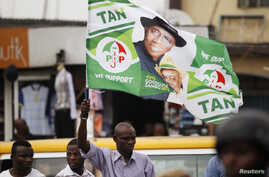 A man holds a flag in support of Nigerian President Goodluck Jonathan at a campaign rally for Lagos governorship candidate Jimi Agbaje of the People's Democratic Party in Lagos, Feb. 3, 2015.