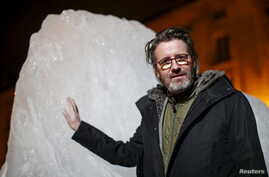 """Olafur Eliasson, a Danish-Icelandic artist, poses in front of a block of ice that was havested in Greenland and transported in a refrigerated container for a project called """"Ice Watch Paris,"""" in Paris, France, Dec. 3, 2015"""