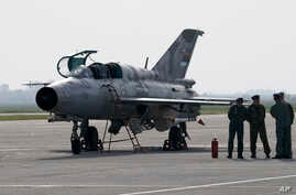 n this April 6, 2016 photo, ground crew stands on the tarmac by a Mig 21 fighter jet, at the military airport Batajnica, near Belgrade, Serbia. Russian President Vladimir Putin has reportedly promised to sign off on a delivery of six MiG-29 fighter j