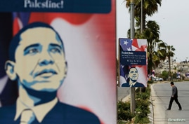 A Palestinian man walks near placards designed by an activist depicting U.S. President Barack Obama, ahead of his visit to the region, in the West Bank city of Ramallah March 12, 2013.