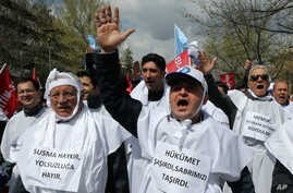 """FILE - Thousands of civil servants and members of Turkish unions wear placards that read """"no to corruption"""" as they march to protest against the government's new labor regulations and economy policies in Ankara, April 4, 2015."""