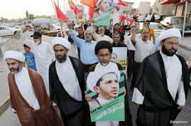 FILE - Protesters hold photos of Sheikh Ali Salman, Bahrain's main opposition leader and Secretary-General of Al-Wefaq Islamic Society, as they march asking for his release in the village of Jidhafs, west of Manama, Bahrain, June 16, 2015. Bahrain se