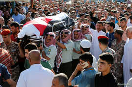 Jordanian soldiers and relatives of Belal Al-Zuhbe, one of the solders killed in an attack on a border military post near a camp for Syrian refugees, carry his body during his funeral at Nahleh village in the city of Jerash, north of Amman, Jordan, J