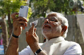 "FILE - Hindu nationalist Narendra Modi, the prime ministerial candidate for India's main opposition Bharatiya Janata Party (BJP), takes a ""selfie"" with a mobile phone after casting his vote at a polling station during the seventh phase of India's gen"