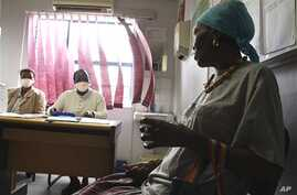Pinky Molefe, right, gets TB medication at a clinic in Alexandra township, north of Johannesburg. (file)