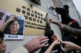 FILE - Protesters try to stick photos of missing booksellers, one of which shows Gui Minhai, at left, during a protest outside the Liaison of the Central People's Government in Hong Kong, Jan. 3, 2016.