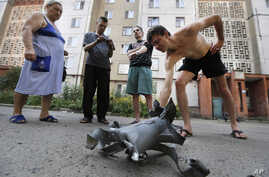 Local residents display fragment of a shell after overnight shelling in Donetsk, eastern Ukraine, Friday, Aug. 8, 2014. At least three civilians have been killed and another 10 wounded in overnight shelling of the main rebel stronghold in eastern Ukr