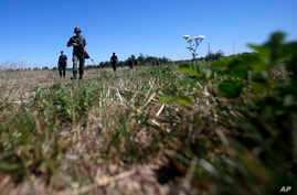 FILE - Serbian army soldiers and border police officers patrol near the border between Serbia and Bulgaria, not far from the border crossing Vrska Cuka, some 250 km (155 miles) southeast of Belgrade, Serbia, Monday, Aug. 15, 2016.