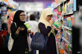 FILE - Malaysian women chat as they shop at a mall in Petaling Jaya outside Kuala Lumpur, Malaysia, Oct. 30, 2014.