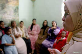 A counselor talks to a group of women to try to convince them that they should not have female genital mutilation performed on their daughters, in Minia, Egypt, June 2006.