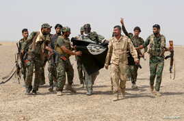 Iraq's Shi'ite paramilitaries and members of Iraqi security forces hold an Islamist State flag which they pulled down in Nibai, in Anbar province, May 26, 2015.