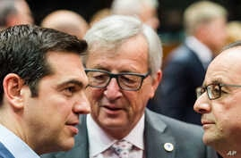 Greek PM Alexis Tsipras speaks with European Commission President Jean-Claude Juncker and French President Francois Hollande during a meeting of eurozone heads of state at the EU Council building in Brussels, July 12, 2015.